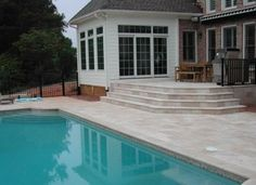 Screen porch converted to 4 season sunroom; wood deck replaced with travertine patio constructed with block; vanishing edge pool and patio installed to create a back yard.