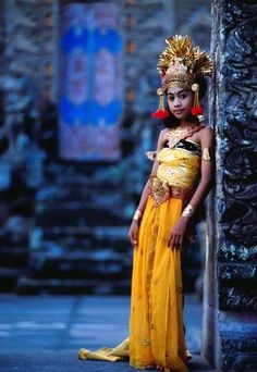 Balinese girl dressed in traditional Hindu garb outside a temple.