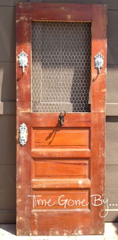 Repurposed door with chicken wire and hooks. Middle hook has three swing arms.   Follow me on FB at www.facebook.com/Timegoneby