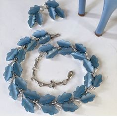 VINTAGE DEMI PARURE OAK LEAF THERMOSET LISNER A beautiful statement piece by well known costume jewelry Lisner known for nature themes, particularly leafs!  The blue moonglow thermoset oak leafs set in rodium? SP setting looks striking!  The necklace has a hook clasp allowing for adjustment & the earrings are clips ons, meaning anyone can wear them!!   I love this set with white t shirt & a chic pair of jeans with heels!! This is a nice demi parure for the Lisner collector or for a piece of…