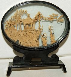 Very detailed scene made of cork and wood within a wooden and glass frame    Made by San You, China - Hand carved to the highest standard with an amazing amount of detail    Beautiful little carving of a pergular type house on a cliff with storks and flowers and trees  £9.99