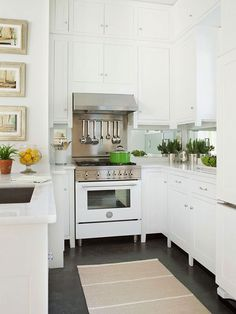 White kitchen, dark floors, mirror backsplash, stainless and white Bertazzoni range cooker