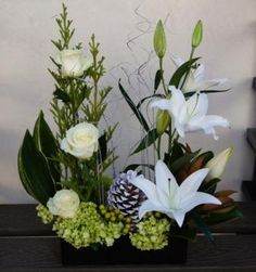 White roses & lilies with a mix of greens. A large white pine cone gives this arrangement a hint of the winter season.