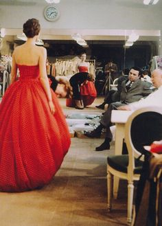 Christian Dior inspects an evening gown prior to a new collection, Paris, 1957