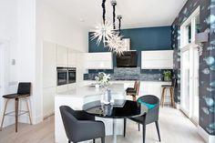 papier peint gris à motifs poissons, peinture murale bleu pétrole et armoires de cuisine blanches