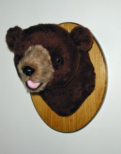 """Plush Brown Bear Head """"Rusty"""" Small Plaque Mount. Rusty is a soft, short plush cinnamon brown bear. He's perfect for wherever you want to add a playful touch. Everyone loves Rusty. He has a sweet smile that shows just the tip of his little pink tongue. PRODUCT SPECS: Ready to hang. Rusty's depth is 12"""" from nose to wall. Girth at shoulder is 24"""". Plaque size is 9"""" x 12""""."""