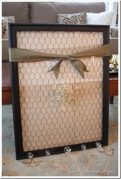Jewelry organizer -- chicken wire over muslin in a frame.  Add small knobs at the bottom for hanging heavier necklaces.
