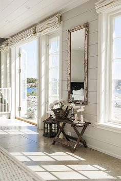 Rustic mirror and beautiful table/vignette in this waterfront living space...perfect.