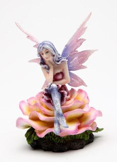 Flower Fairy 3 figurine. This thoughtful fairy with her face resting in her right hand, sits on a full pink, white and yellow rose. She wears blue and white tights, a magenta dress, and blue and pink wings. She will add charm to your home wherever she is placed!