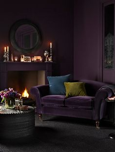 The deep and moody aubergine purple of this living room draws one in, to sit and relax by the fire.