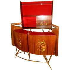 "Italian Bar and back bar  ITALY  Circa 1950's  ITALIAN rosewood Bar and Back Bar set.  Modernist double inlay design on back bar cabinet  Each of the 3 designs are different with red green and yellow accent.  Brass hairpin legs.  with a display vitrine in the back bar cabinet.  Image 10: 2 stools available with red vinyl seat ($950)   Bar dimensions : 52"" w /43"" h / 16 "" d  Back Bar dimensions : 40 "" w /68 "" h / 10 "" d"