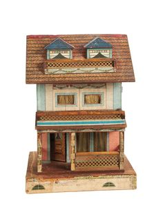 """Lot: 95. Petite American Wooden Dollhouse by Bliss  18"""" (46 cm.) A wooden two-story dollhouse features a front porch with metal grill railing that matches the metal grill trim on second-story balcony and below the attic dormer windows. There is an opening front door,and four eisenglas windows at the front. The house has lithographed paper cover with a variety of shingles,windows (some curtained,some with stained glass),garlands of flowers,and other architectural details. The entire front…"""