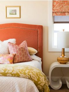 gorgeous coral upholstered head board with yellow patterned throw and gold funky lamp