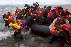 Refugees and migrants struggle to jump off an overcrowded dinghy on the Greek island of Lesbos, after crossing a part of the Aegean Sea from the Turkish coast, October 2, 2015. A record number of at least 430,000 refugees and migrants have taken rickety boats across the Mediterranean to Europe this year, 309,000 via Greece, according to International Organization for Migration figures. REUTERS/Dimitris Michalakis