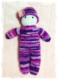 Hand knitted doll with a single crocheted flower on her hat.