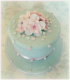 Such a pretty cake -- This cake is a Ameretto Lovers dream .... rich almond sponge made with marzipan, laced with ameretto syrup, filled with ameretto buttercream, covered with fondant icing, decorated with hand made sugar blossoms and hand piped pearls.