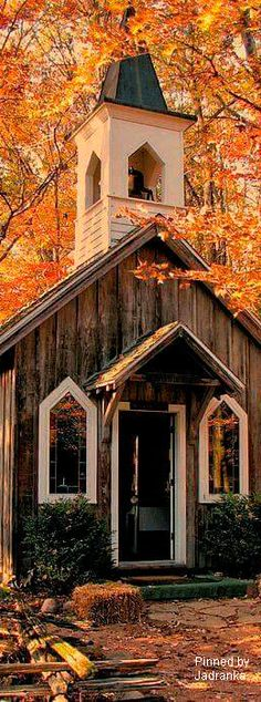 Old weathered church surrounded by an orange autumn