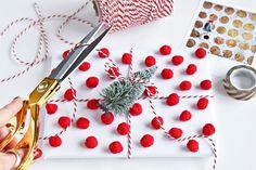 Fotobuch-Weihnachtsgeschenkverpackung Variante 3: Weißes Geschenkpapier mit roten Pompons & kleiner Schneetanne