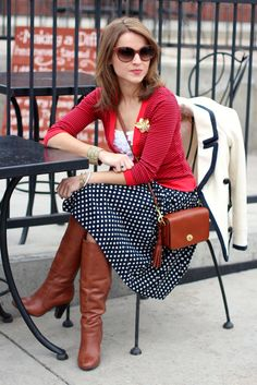 Navy and white polka dot skirt. White blouse. red cardigan. Brown boots. Brown purse. Brown satchel. White coat with black piping.