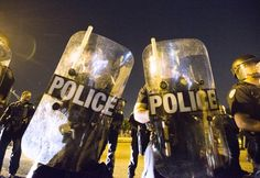 Protesters face off with  police in riot gear across the street from the Baton Rouge, La., Police Department on July 8, 2016, in the wake of the fatal police shooting of Alton Sterling.