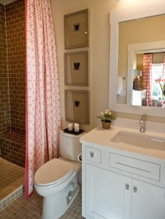 bathroom - walk-in shower + a custom shower curtain with a contemporary print in a hot coral shade + cute mirror frame