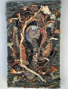 Enchanted by Karen Klassen (Edmonton, AB),15 x 25 inches.  Ammonite, turquoise quartz, driftwood, shale, pebbles, mudstone, vandanite, porcelain, mirror, hemimorphite, pottery, china, pennies, malachite, pyrite, blown glass, obsidian, copper, cerusite galena, and pale peach barite blades, millefiori and granite