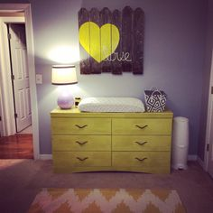 "Love the yellow pop of color in this gray nursery, especially the DIY ""Love"" wall art made from old fence posts!"