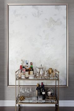 Luxurious gray dining room boasts an Arteriors Home Lisbon Bar Cart positioned on wood floors in front of a large light gray abstract painting mounted on a gray grasscloth covered wall.