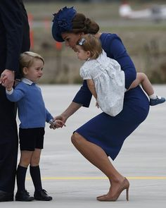 Catherine, Duchess of Cambridge held her son Prince George's hand while carrying Princess Charlotte as Prince William spoke with officials after arriving in Victoria