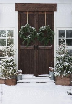 Gorgeous snowy winter scene with dark wood French front doors, potted outdoor Christmas pine trees and metal buckets of decorative wood, with matching juniper wreaths on the doors.