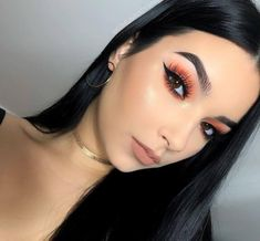 Add a pop of color to your look with a bright peach eyeshadow.