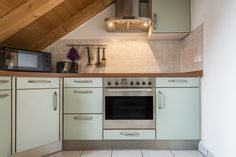 Kitchen in attic with low sloped wood ceiling.  You definitely need to watch your head working in this space.
