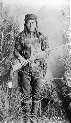 Peaches (Tsoe), a White Mountain Apache scout; full-length, holding rifle.   Photographed by Ben Wittick, ca. 1885.