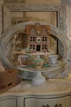 Gold glittery Christmas house on a cake plate with tea cups....Precious I really like this idea for displays.