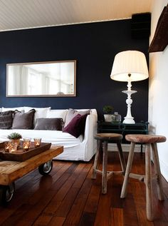 This room is wonderful: Dark, bold wall highlighted with a simple white slip covered couch, a bright lamp with great lines, and a reflecting light/space mirror. Rustic wood accents and a variety of fabric muted color pillows and of course a little greenery tie the space together. Love!