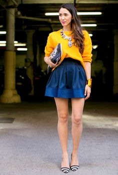 yellow chunky sweater, blue high-waisted flouncy mini skirt, oversized clutch and striped flats