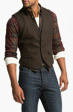 Este es una camisa de cuadros, unos jeans y un chaleco. Se puede vestir en una…