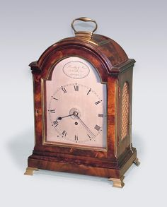A fine quality early 19th Century mahogany domed top Bracket Clock having brass carrying handle and moulded decoration raised on original brass ogee bracket feet retaining original mahogany wall bracket. Circa 1810