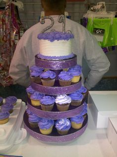 "Small Birthday Cake and matching cupcake tower - This was for my daughter's gymnastics coach's 21st birthday.  The cake is a I believe a 6 inch cake.  The ""21"" is made of gumpaste and sprinkled  with silver disco dust.  The cupcakes are chocolate and some white cake with matching  purple buttercream and silver dragees."