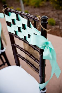 Dark chivari chairs with ribbon woven thru the back of the chair and tied with a bow..simple and elegant