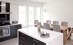 Ruokatilaan haluttiin suuri pöytä, jonka ääreen mahtuu isompikin porukka. Kustavinpuun kahdeksan hengen tamminen ruokapöytä hankittiin Tilamarista. Pehmeät tuolit ovat Aada Sisustuksesta. | Tyylikäs musta tuo keittiöön luksuksen tuntua | Koti ja keittiö