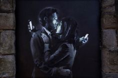 Mobile Lovers: [Graffiti artist] Banksy has dropped a new mural in the UK, and the subject is something we can all relate to. The piece, called 'Mobile Lovers,' depicts a couple embracing, but instead of gazing lovingly into each other's eyes, they're wrapped up in their cellphones.""