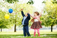 Little brother and sister having fun with balloons in the park