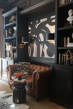 Leather tufted sofa, greyhound statue, fluted side table, built-ins to create a nook, lighting