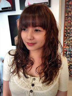 long layered permed hair with straight bangs