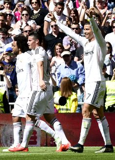 Marcelo and James Rodriguez celebrate Cristiano Ronaldo's goal during the Spanish league football match Real Madrid CF vs Granada FC (4-0) at the Santiago Bernabeu stadium in Madrid on April 5, 2015.