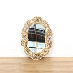 This coastal mirror is featured in a wood with a glued on shell motif in natural beige, whites and purples. This beach chic accent mirror has an oval frame with scalloped edges and shell trim. Great for a cottage by the sea style! #coastal #decor #mirror #sandiegovintage #vintagefurniture