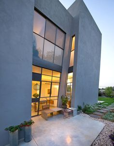 This home in Israel has a slanted wall that towers over the outdoor patio.