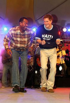 """Help for Haiti Prince Harry wears a T-shirt bearing the slogan, """"Haiti we care,"""" as he dances on stage with a local singer at the fund-raising concert at the Farley Hill national park on Jan. 31, 2010, in Bridgetown, Barbados."""