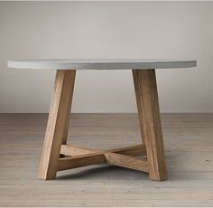 """RH's Salvaged Wood & Weathered Concrete Beam Round Dining Table:Our table pairs a 3""""-thick slate grey concrete top with the natural beauty of solid salvaged pine timbers from 100-year old buildings in Great Britain."""